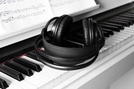 Piano with headphones and music notes close up Stock Photo