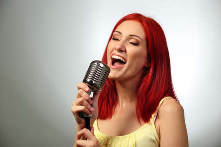 Beautiful young woman with microphone on gray background Stock Photo