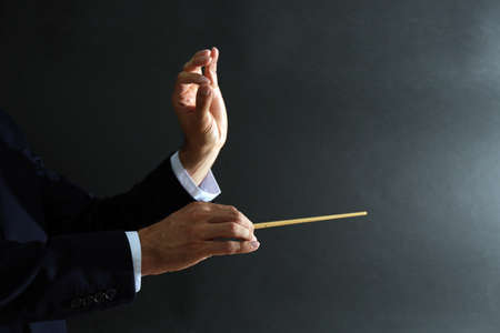 Music conductor hands with baton on black background Stock Photo - 93231307