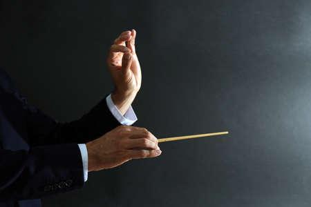 Muziek dirigent handen met stokje op zwarte achtergrond