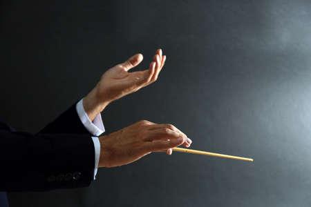 검은 배경에 지휘봉과 음악 지휘자 손