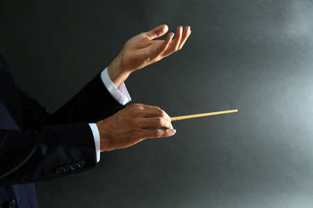 Muziek dirigent handen met stokje op zwarte achtergrond Stockfoto