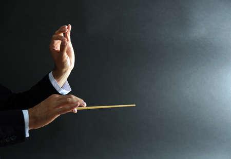 Mãos de maestro de música com bastão em fundo preto Foto de archivo - 93385933