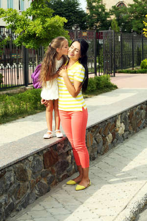 Beautiful school girl with mother walking outdoors