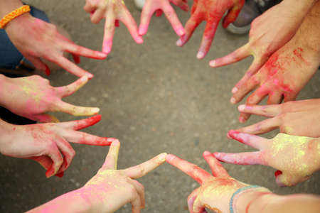 Hands of young people with Indian dyes on Holi color festival 스톡 콘텐츠