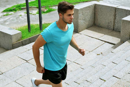 Young man jogging at stairs outdoors