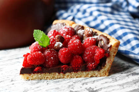 Piece of tart with fresh raspberries, on wooden background Stock Photo