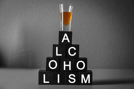 Glass of strong drink and cubes with word ALCOHOLISM on table