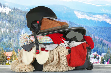 Open suitcase with stuff for winter vacation on table against mountain landscape