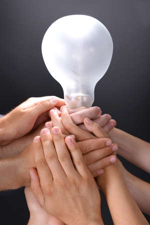 Light bulb in hands on grey background Stock Photo