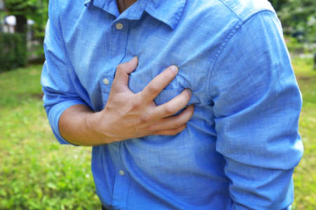Man having chest pain - heart attack, outdoors Stock Photo