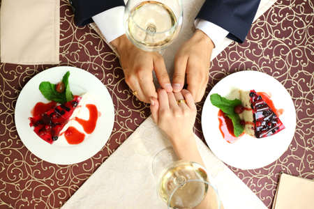 Hands of newlyweds at table in cafe, closeup