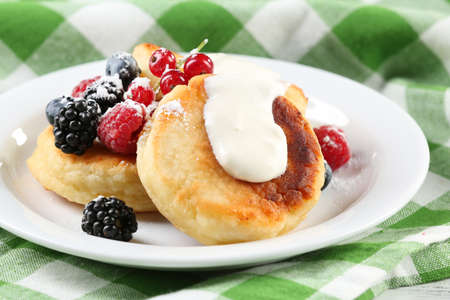 Fritters of cottage cheese with berries in plate, closeup Stock Photo