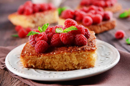 Fresh pie with raspberry in white saucer on wooden table, closeup