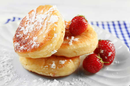 Fritters of cottage cheese with strawberry and sugar in plate on table, closeup Stock Photo