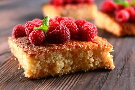 Fresh pie with raspberry on wooden table, closeup
