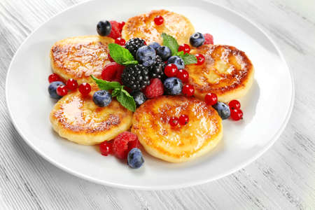 Fritters of cottage cheese with berries in plate on wooden table, closeup Stock Photo