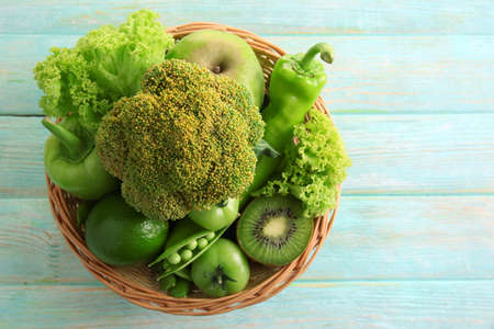 Fresh green food in wicker basket on wooden background