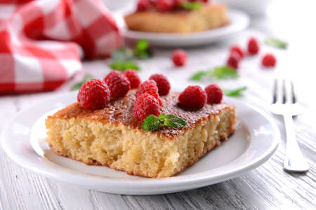 Fresh pie with raspberry in white plate on wooden table, closeup Stock Photo