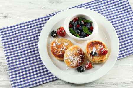Fritters of cottage cheese with berries in plate on table, closeup Stock Photo