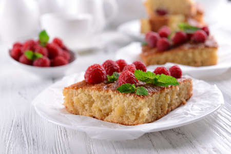 Fresh pie with raspberry in saucer on wooden table, closeup