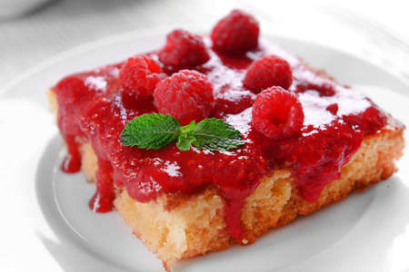 Fresh pie with raspberry jam in white saucer on wooden table, closeup
