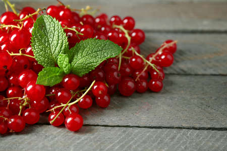Ripe red currant on wooden background