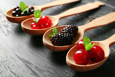 Forest berries in wooden spoons on color background Stock Photo