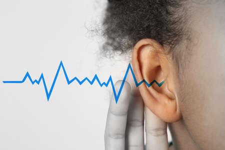 Ragazza afroamericana con sintomo di perdita dell'udito su sfondo chiaro% 00 Archivio Fotografico