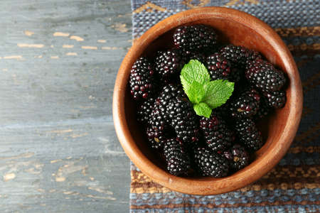Ripe blackberry in bowl on color wooden background Stock Photo