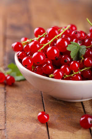 Fresh red currants in bowl on wooden table close up
