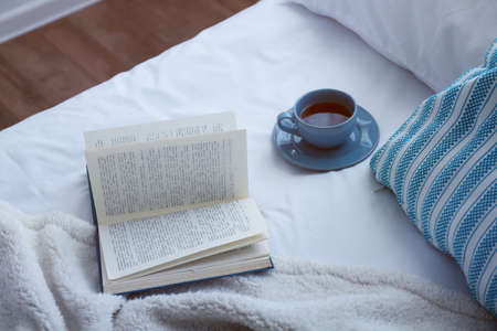 Open book and cup on bad close-up Imagens