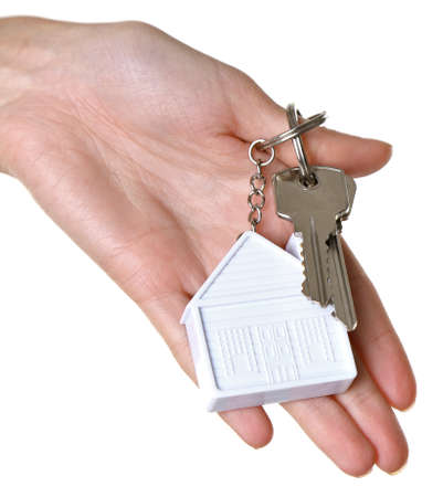 Female hand holding keys with house key chain isolated on white Stock Photo