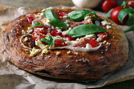 Greek homemade pizza with ham,onion, roasted tomato, creamy feta on wooden table background