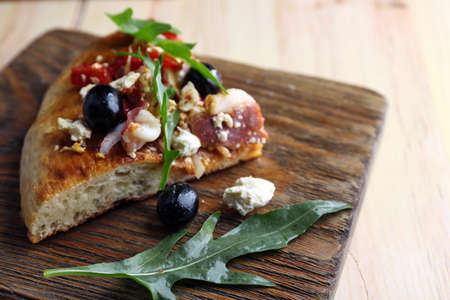 Piece of homemade pizza on wooden board background