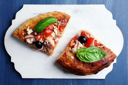 Piece of homemade pizza on tray, on wooden board background