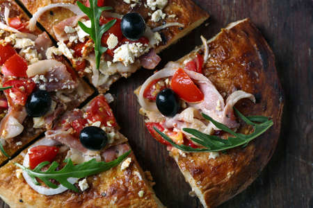 Greek homemade pizza with ham,onion, roasted tomato, creamy feta on wooden board, on table background