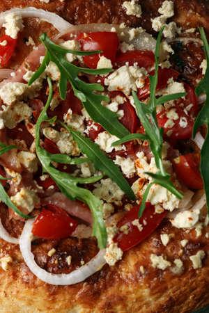 Greek homemade pizza with ham,onion, roasted tomato, creamy feta, close-up