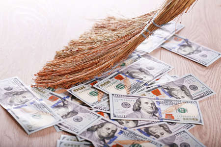 Dollars and broom on wooden floor, closeup