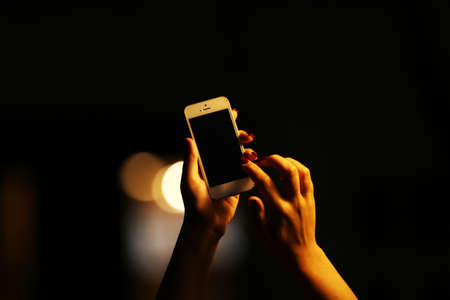 Female hand with mobile phone on blurred night lights background 스톡 콘텐츠