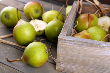 Ripe pears in wooden box on table close up