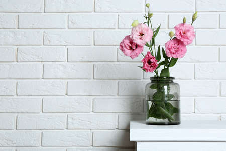 Beautiful flowers in vase on brick wall background Stock Photo