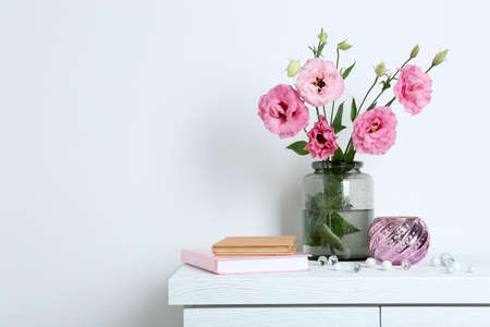 Beautiful flowers with books on wall background Stock Photo