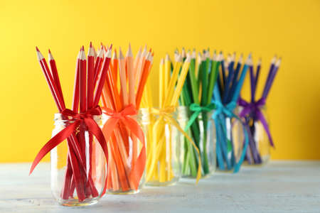 Bright pencils in glass jars on wooden table, on yellow background 写真素材