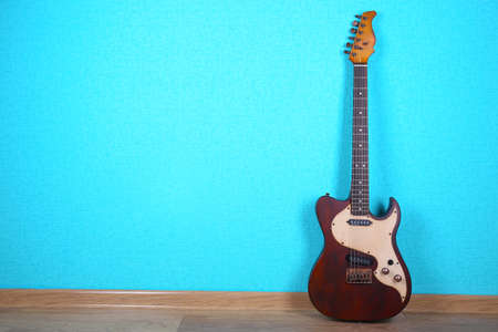 Electric guitar on blue wallpaper background