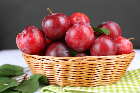 Ripe plums in wicker bowl on wooden table with napkin on dark background