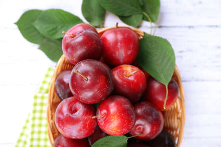 Ripe plums in wicker bowl on wooden table with napkin, closeup