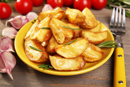 Baked potato wedges on wooden table, closeup Stock Photo