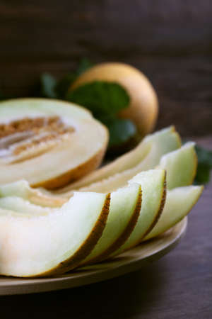 Slices of ripe melons with green leaves on table close up Stock Photo