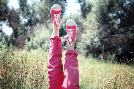 Female legs in colorful sneakers outdoors Stock Photo
